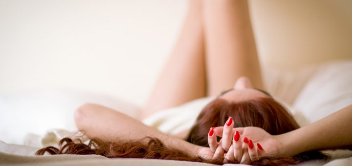 Girl laying on bed with red nails