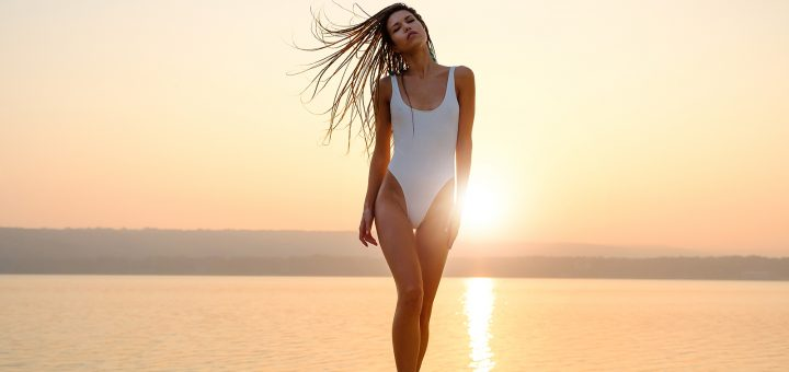 Young woman in strings swimsuit stands on the beach in sunrise