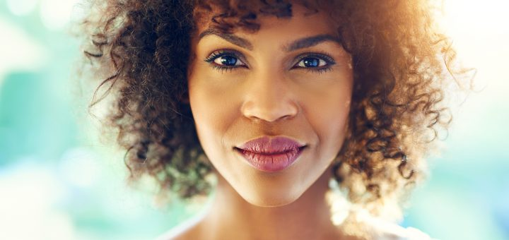 Portrait of perfect afro-american woman looking at camera with semi-smile on blurred background.